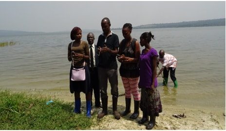 NAPE staff carrying out GPS mapping to establish the extent of buffer zone meter encroachment on Lake Victoria in Kalangala